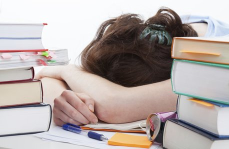 Girl sleeping on work essay stock image